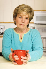 picture of beautiful senior woman  - Senior woman holds a coffee mug looking sad - JPG