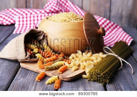 Different types of pasta in containers on wooden background