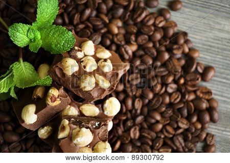 Chocolate with mint and coffee beans on wooden table, closeup