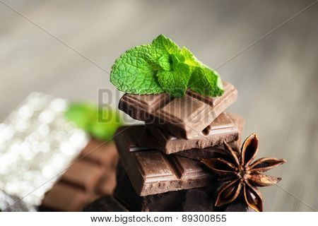Set of chocolate with spices on wooden table, closeup