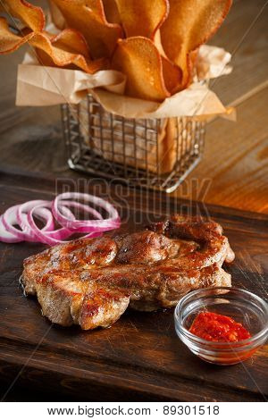 Delicious steak with chili sauce and chopped onion rings