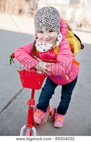Portrait of cute toddler girl in pink jacket with the scooter