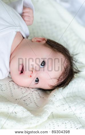 Sweet Little Baby Daughter On White Woolen Blanket