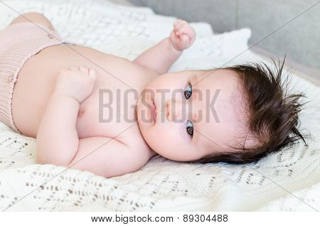 Cute Newborn Baby Girl Lying On Woolen Blanket With A Toy