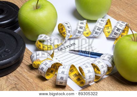 Close Up Of Paper With Diet Plan, Apples, Dumbbells And Measure Tape