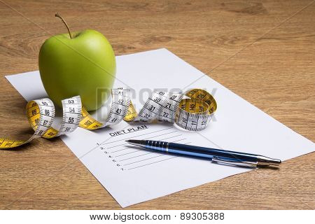 Paper With Diet Plan, Pen, Apple And Measure Tape On Table