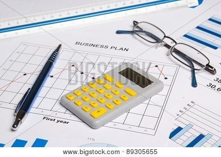 Close Up Of Business Papers With Graphs, Charts, Glasses, Pen And Calculator
