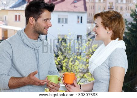 Young couple drinking coffee at the terrace, talking, smiling.