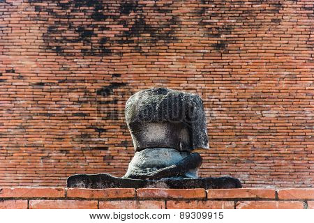 A Headless Buddha Sitting In Front Of Brick Wall In Ayutthaya, Thailand