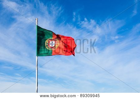 Portugal Flag Waving On The Wind Over A Cloudy Blue Sky