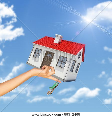 House and keys in womans hand