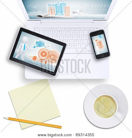 Tablet and mobile phone on laptop with coffee cup