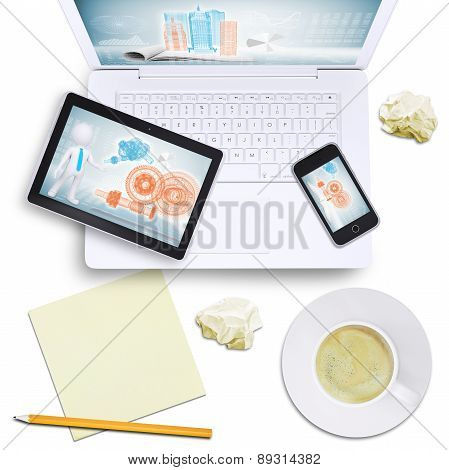 Tablet and mobile on laptop with crumpled paper