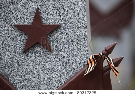 Red star and the Ribbon of Saint George at the Soviet War Memorial with graves of Soviet soldiers fallen in the last days of World War II at the Olsany Cemetery in Prague, Czech Republic.
