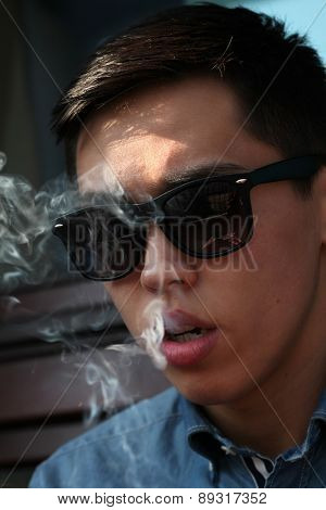 Handsome young Asian man smoking and looking downward