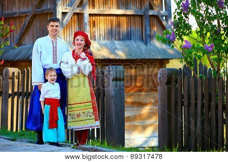 Portrait Of Ukrainian Family Dressed In Traditional Costumes Near The House