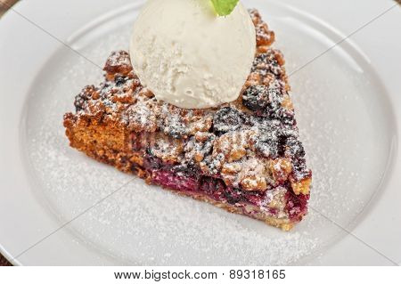 Crumble pie with black currants. English dessert with creamy ice cream