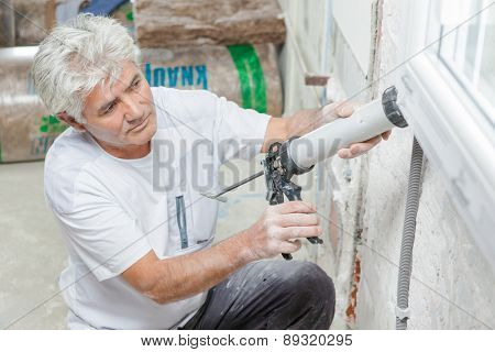 Handyman caulking a window frame