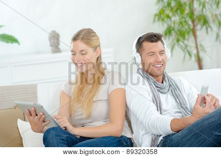 Couple relaxing on the sofa with their gadgets