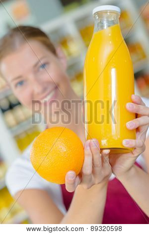 Shop assistant holding orange and juice