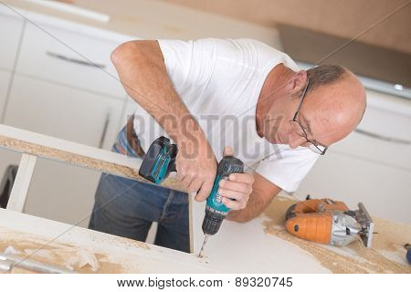 Carpenter drilling into a wooden surface