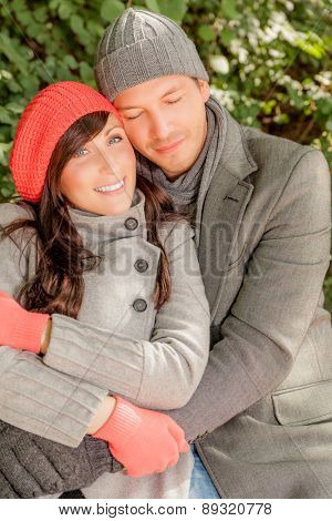 embracing couple sitting colder day outdoors