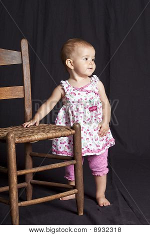 Baby Girl Standing Next To Chair