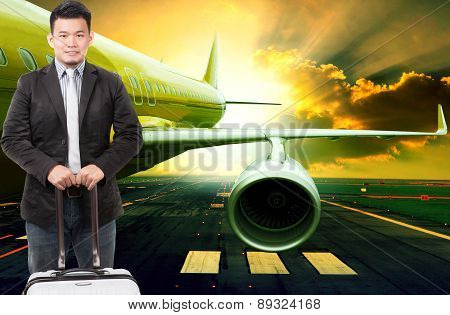 Young Business Man And Traveling Luggage Standing In Front Of Passenger Jet Plane Flying Over Airpor