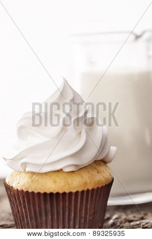 Cupcakes With White Cream On Background Of A Carafe Of Milk