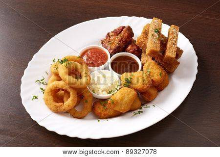 Fast food. Dish with snacks and sauces, close-up