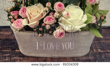 Fresh Roses In A Vase With Love Sign