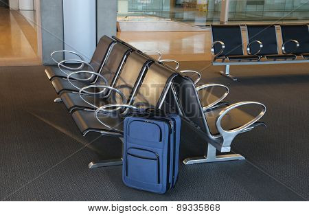 Blue suitcase at an airport lobby.