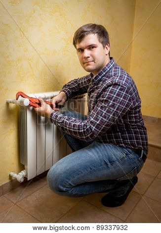 Young Man Holding Pliers And Installing Radiator Valve