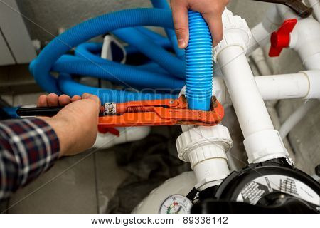 Plumber Connecting Two Pipes With Red Pliers