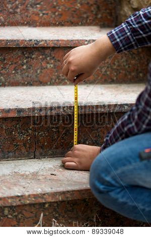Closeup Of Worker Measuring Height Of Stone Steps