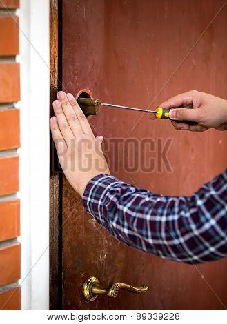 Closeup Of Carpenter Fixing Door Lock With Screwdriver