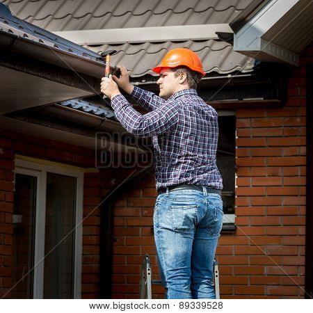 Carpenter Hammering Roof Boards With Hammer
