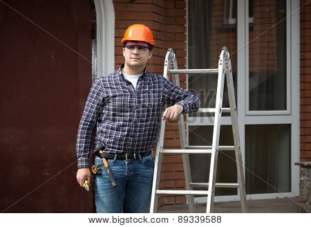 Smiling Worker In Hard Hat Leaning Against Metal Ladder