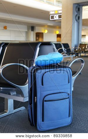 Blue suitcase and pillow at an airport lobby.