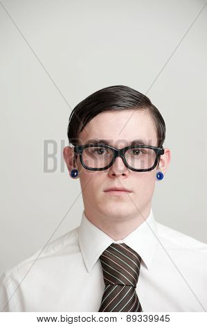 Portrait - Young Man With Eye Glasses & Pierced Ears Wearing Business Shirt & Neck Tie