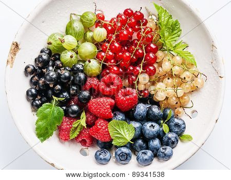 Mix Of Fresh Berries With Leaves In Vintage Ceramic Colander On White Background