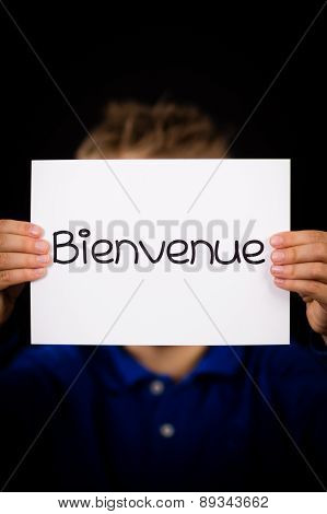 Child Holding Sign With French Word Bienvenue - Welcome