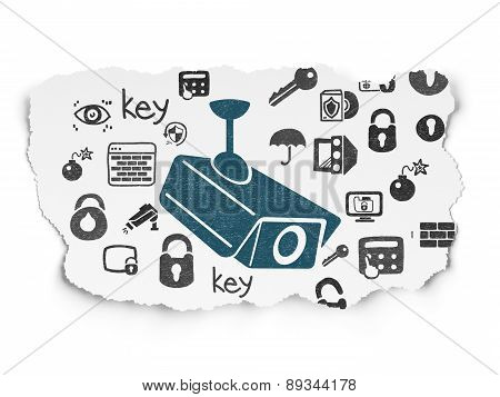 Security concept: Cctv Camera on Torn Paper background