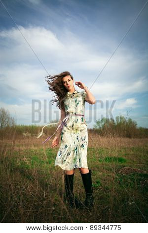young woman in summer  dress enjoy in warm wind in grass field, full body shot