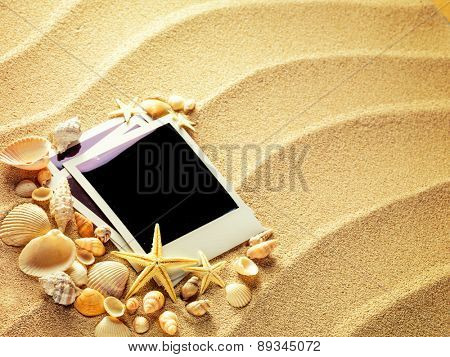 Old style empty photo cards lying on a sea sand and framed with shells. Sunny summer like background. Space for your text.