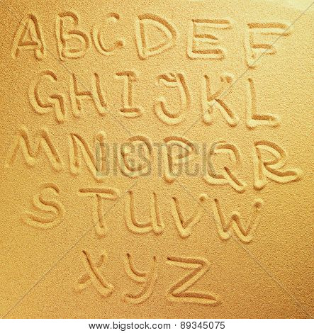 Alphabet letters handwritten in the sand on the beach