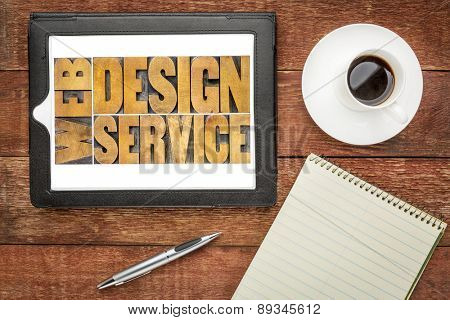 web design service word abstract  in letterpress wood type on a digital tablet, top view of a rustic barn wood table with coffee and notepad