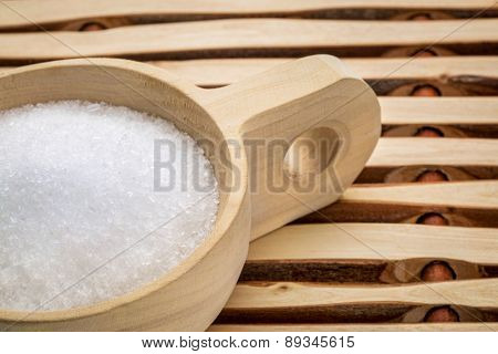 Magnesium sulfate (Epsom salts) in a rustic wooden scoop - relaxing bath concept
