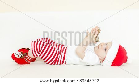 baby girl as Santa Claus holding a bell