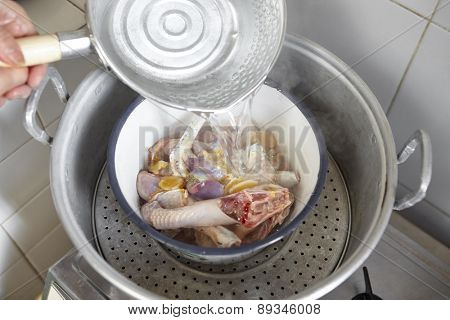 Pouring boiled water to the raw chicken in the bowl